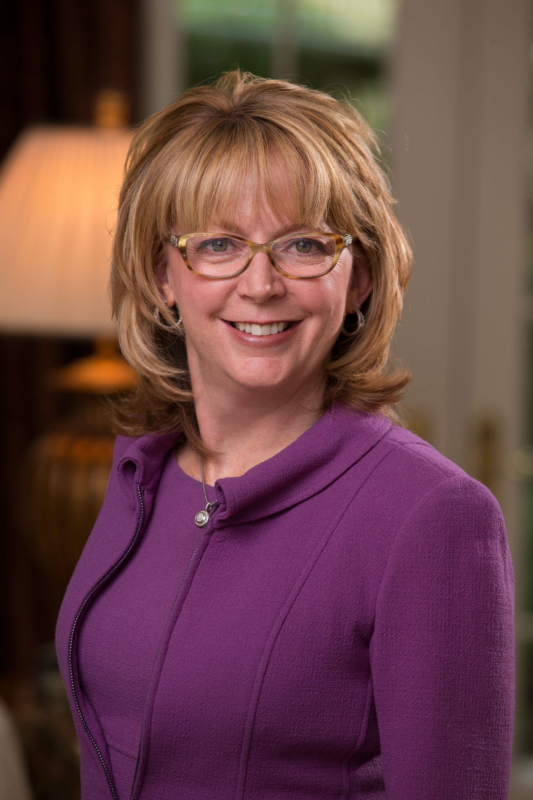 Deborah Majoras, P&G's Chief Legal Officer, wears a plum blouse and looks to camera.