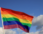 A rainbow Pride flag waves in front of a blue sky.